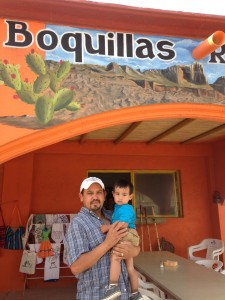 Lifetime Boquillas resident Ventura Falcon poses with his 1-year old son outside of the family restaurant (Travis Bubenik/KRTS)