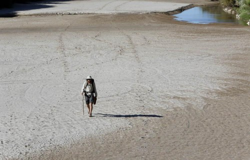 Colin McDonald walks along the riverbed of the Rio Grande on his way to the Texas state line. (NPR/Erich Schlegel)