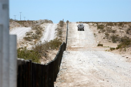 A Border Patrol veihicle drives past vehicle barriers near Deming, NM. (Jim Greenhill via Flickr/Creative Commons)