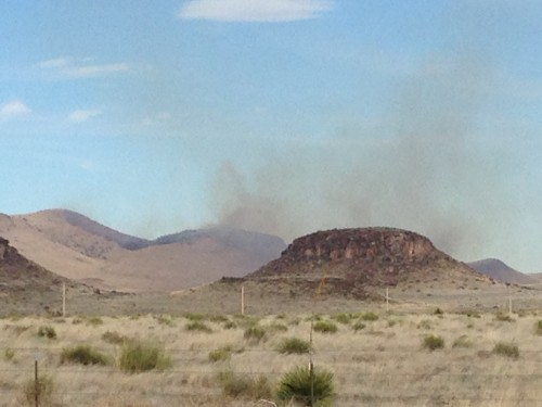 A wildfire burns south of Fort Davis on the east side of SH 17 Sunday evening. (Travis Bubenik / KRTS)