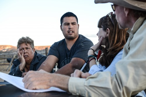 Crew members David Keller and Danielle Acee consult maps and discuss search routes with Velador's relatives.