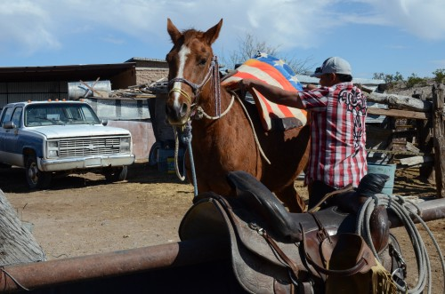 Velador's relative saddles one of Parada's horses with a blanket reflecting U.S. heritage.