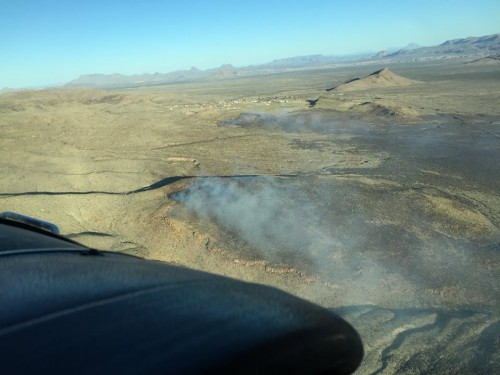 Aerial photo of the wildland fire burning in the Park on Tuesday Feb 2, just East of Panther Junction. The housing community and Headquarters is visible just to the left (South) of the prominently pointed Lone Mountain. Charred black visible in the photo's foreground. (National Park Service)