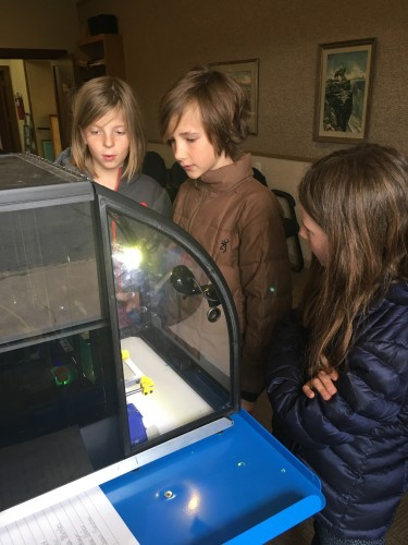 From left to right, Francis Benton, Victor Culbertson and his sister, Louise Culbertson wait for their 3D designs to be printed at the Marfa Public Library. New grants are bringing 3D printers to several border libraries in Texas. (Lorne Matalon)