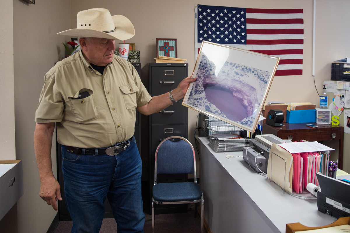 Winkler County Sheriff George Keely holds a years-old photograph of a Winkler County sinkhole that has since grown far bigger. (Rafael Aguilera)