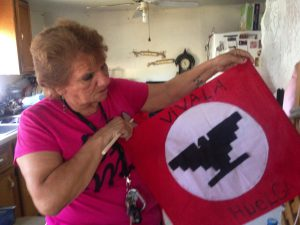 Daria Vera holds a banner from the 1966 farmworkers strike in Texas. (Joy Diaz/KUT)