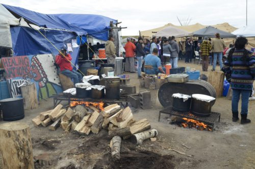Meals cook over a fire to feed hundreds of people at a camp near the Standing Rock Sioux Reservation in North Dakota. (Amy Sisk)