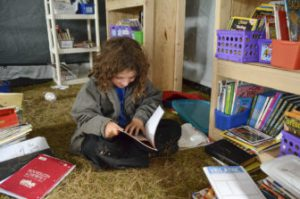 Kai Knott, 9, flips through a book in the literacy room of the school at camp. The makeshift school is contained in several large tents for now, but those in charge of the facility plan to build a more permanent structure to endure the winter. (Inside Energy)