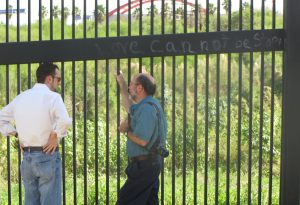 Michael Seibert (right) and visitor Dr. Ryan Van Ramshorst talk about the border wall in Brownsville. (Marsha Griffin)