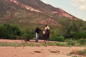 Tom Michael of KRTS interviews a vaquero from northern Mexico, in Brewster County, Texas, August 2005. (Caroline Oman)