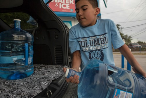 Eric Razo, 11, helped load five-gallon water containers into the back of his aunt's vehicle during a recent water outage in the part of Rio Grande City serviced by Union Water Supply Corporation. (Spencer Selvidge)