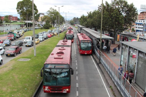 Transmilenio's buses enter and exit a rail-like raised platform beside a snake of traffic on the left. The system, under scrutiny by US urban planners, has transformed mass transit in Bogotá, one of South America's great metropolises. (Lorne Matalon)