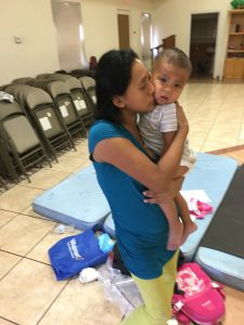 Beatriz Escalante holds her son at the Yuma church shelter where she'll stay the night after crossing into the U.S. to seek asylum. (Michel Marizco)