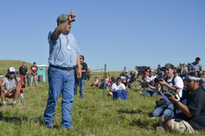 Standing Rock historic preservation officer Jon Eagle Sr. addresses a crowd of protesters gathered at a camp near the Dakota Access Pipeline construction site along the Missouri River. (Amy Sisk)