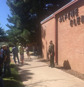 A Border Patrol agent keeps watch as parents arrive to take their children home from Alpine Elementary School after Thursday's shooting at nearby Alpine High School. (Pete Szilagyi)